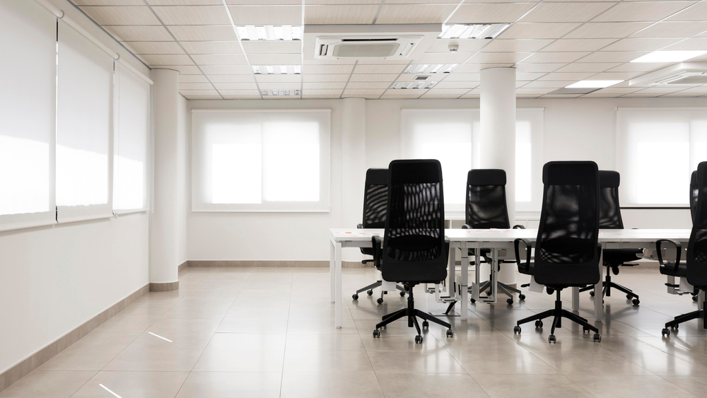 Open space office with a desk and black chairs, white walls and white roller blinds