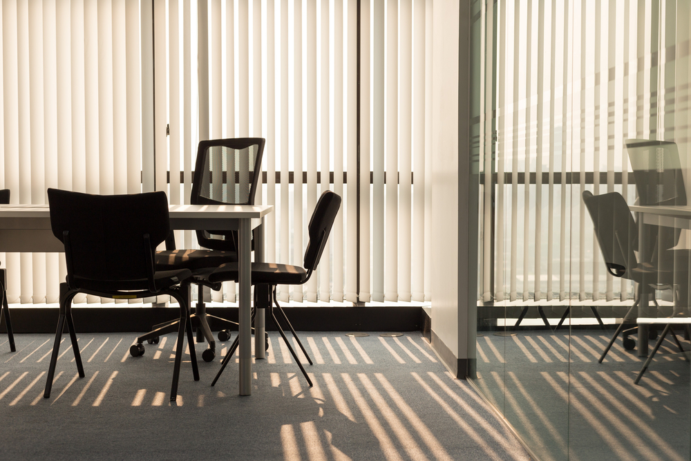 Office interior with light shining through white window shutters