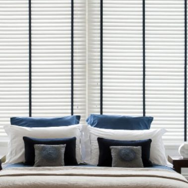 White venetian blinds patterned with black fabric in a modern bedroom