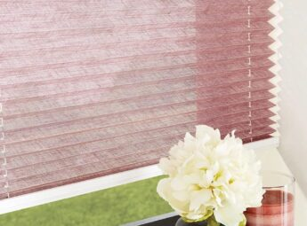 Pink pleated blinds on grey framed window