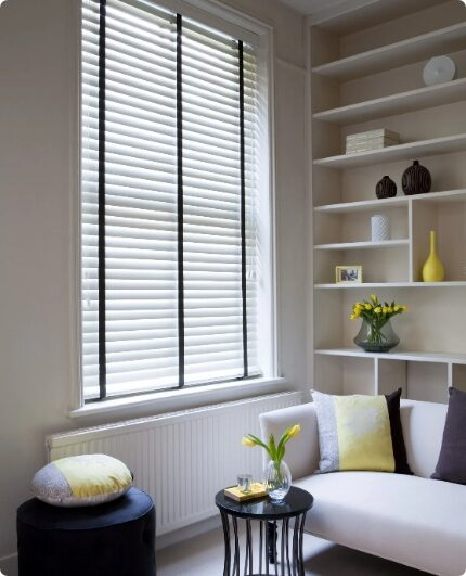 white venetian blinds patterned with black fabric in a modern living room
