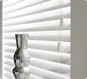 White venetian blinds behind a silver ornament