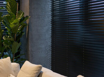Black wooden venetian blinds in a grey room with a large green plant and a cream sofa