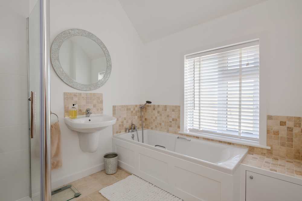 White faux wood blinds decorating a white bathroom, with cream patterned tiles