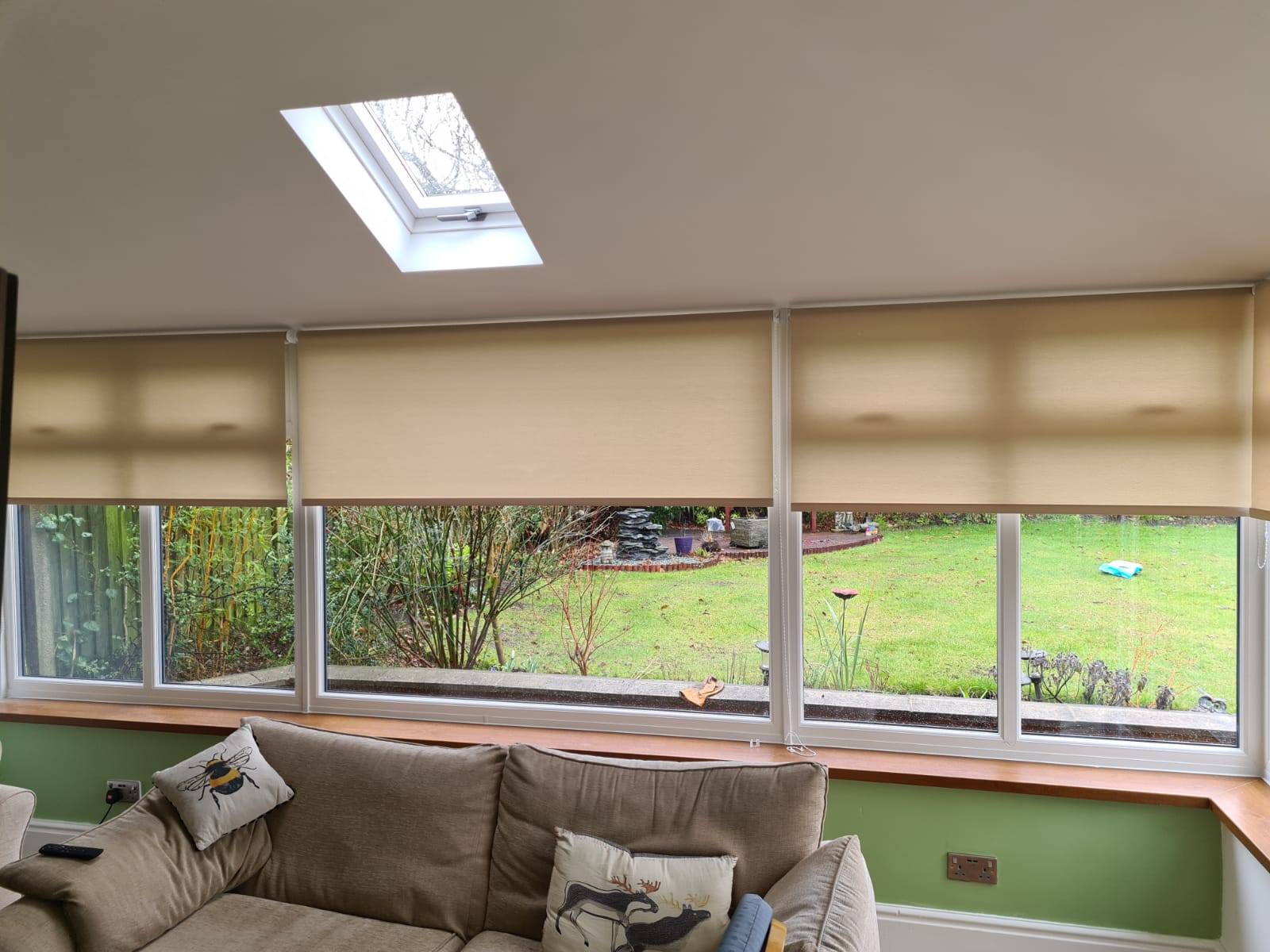 Beige roller blinds partially closed over conservatory windows, with a brown sofa in the foreground and a garden visible outside.