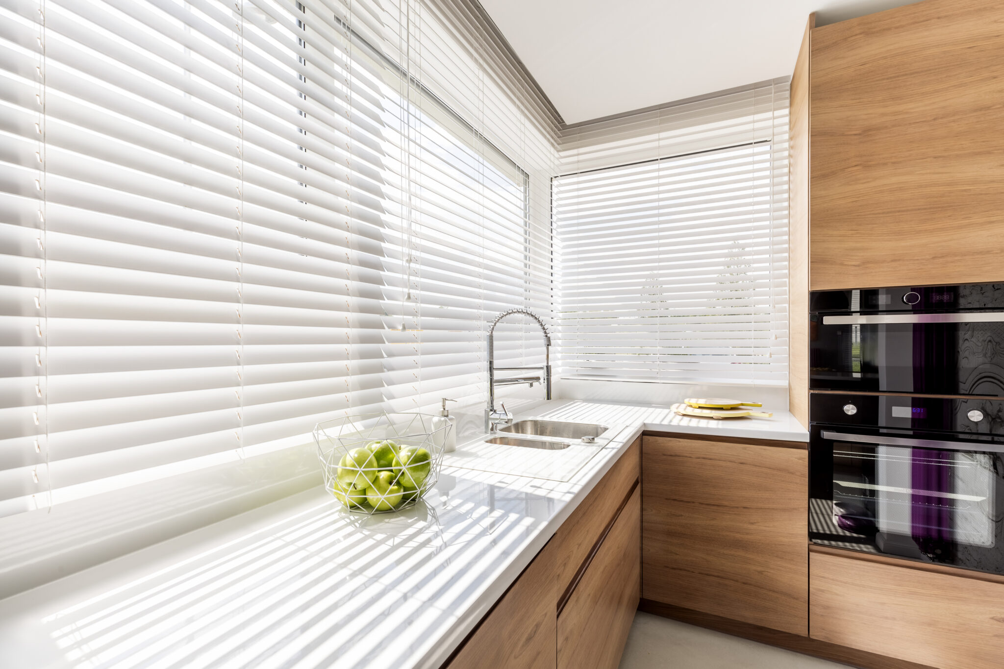 White venetian blinds in a kitchen space that are half open.