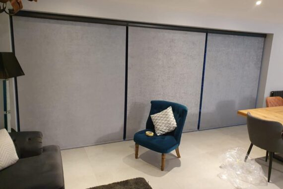 Grey motorised blinds covering a three-panel patio door, with a blue chair on a cream carpet in the foreground, a dark grey sofa to the left, and the end of a wooden table to the right.