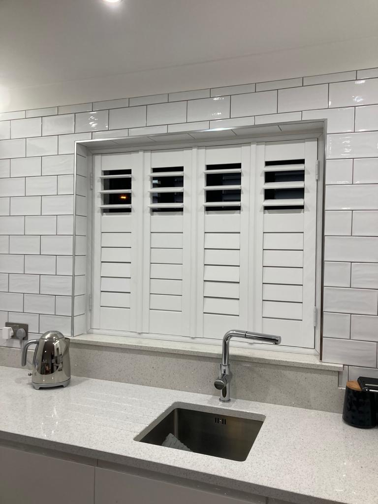 White shutters closed above a kitchen sink and white countertop, with the surrounding wall tiled in white.