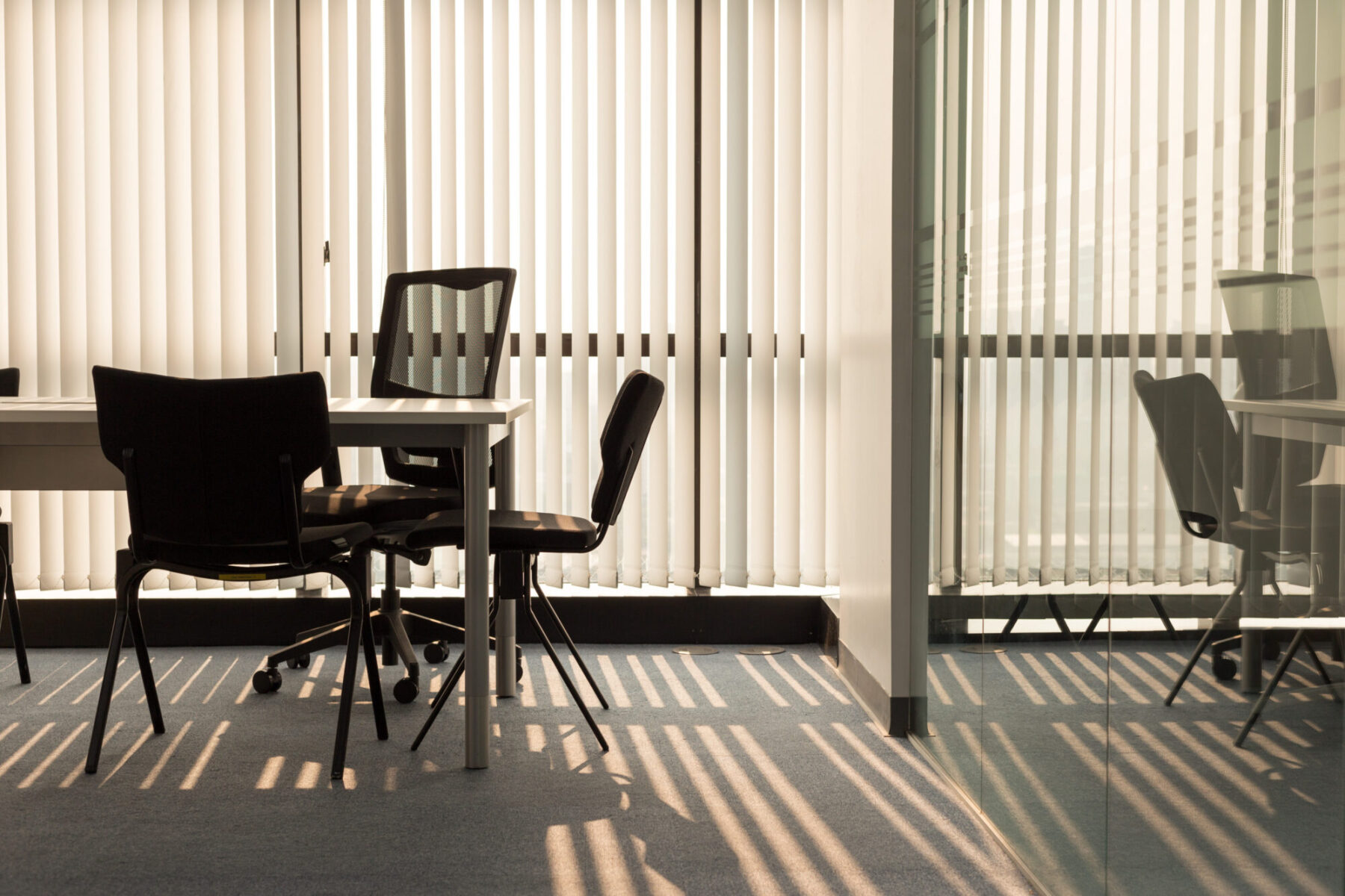 Black office chairs around a white desk, with windows covered by vertical blinds and the background, all reflected in a glass partition to the right.