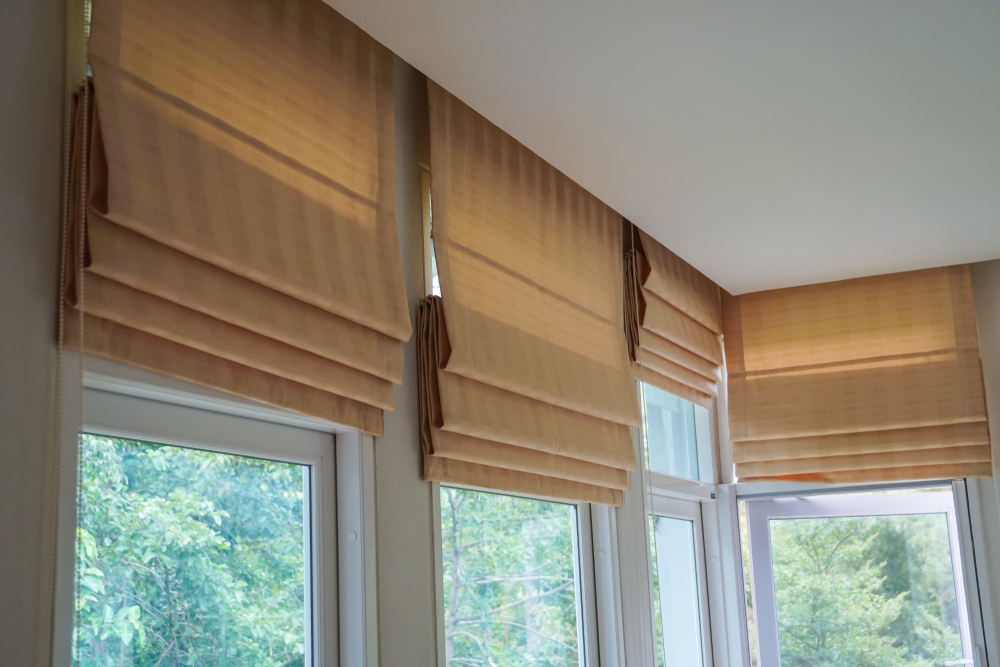 Set of four brown roman blinds on arched windows