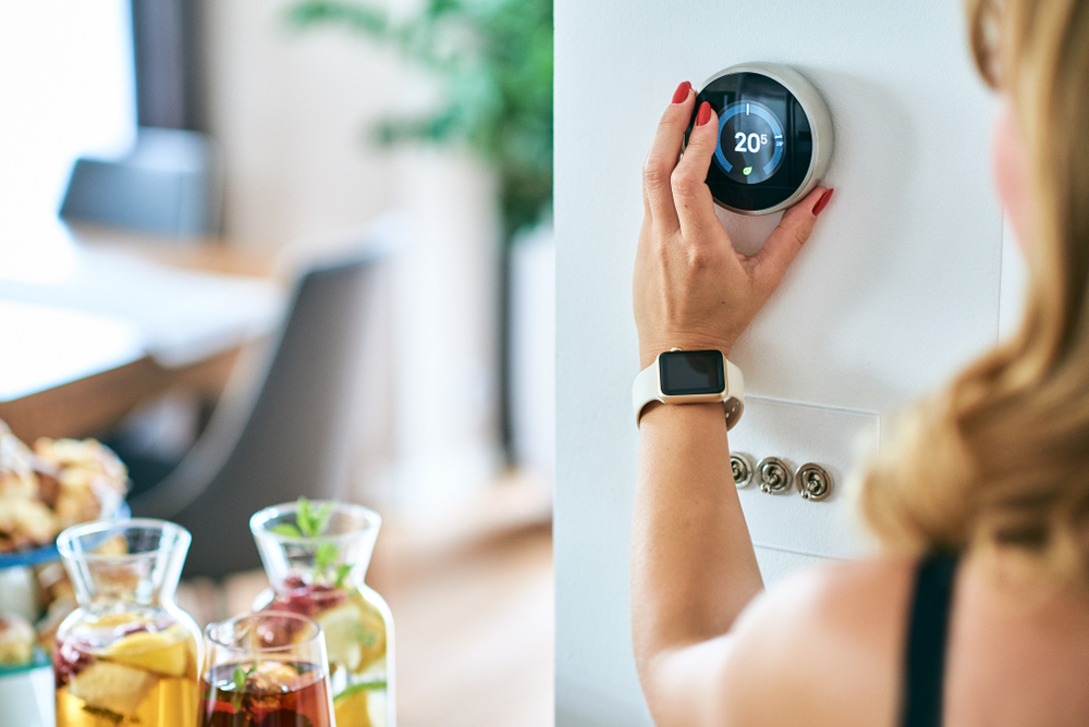 Woman adjusting the temperature on a thermostat