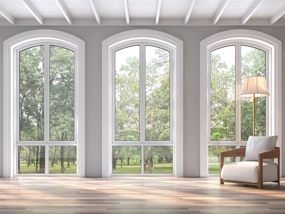 Image of three arched windows with white frames in a grey living room