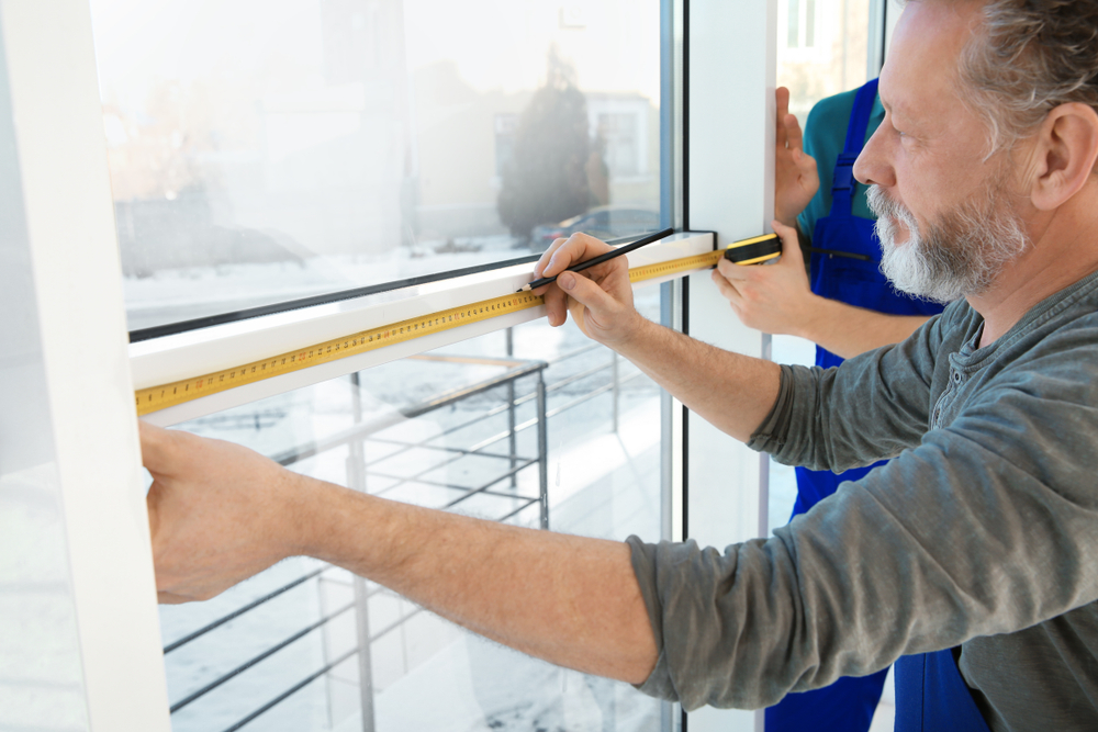 Photograph of two men measuring a long window in order to adjust perfect fit blinds