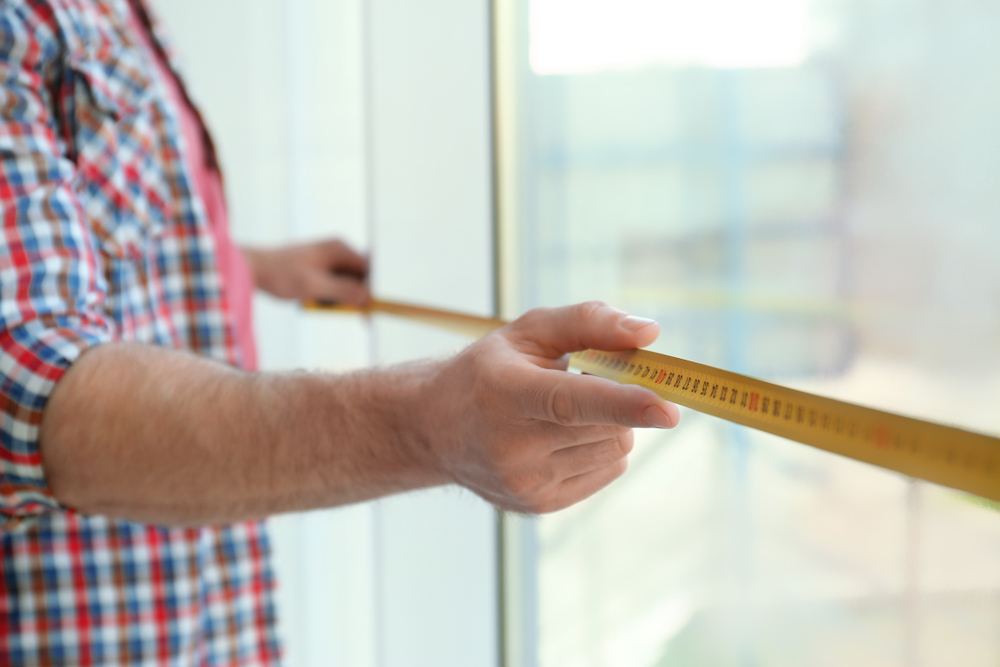 Close-up view of a man measuring a window to fit blackout vertical blinds