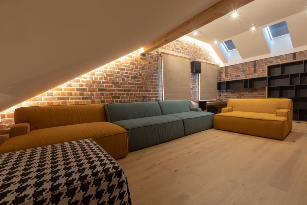 Attic room with four different yellow, blue and black/white couches and skylights with blinds