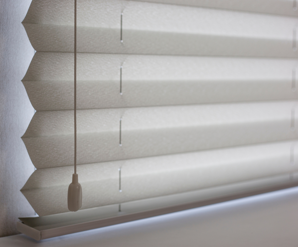 Close-up image of pleated white/grey blinds