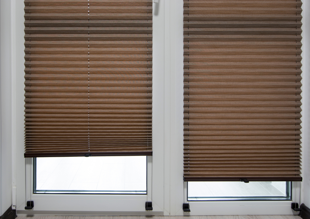Brown pleated fabric blinds on two windows