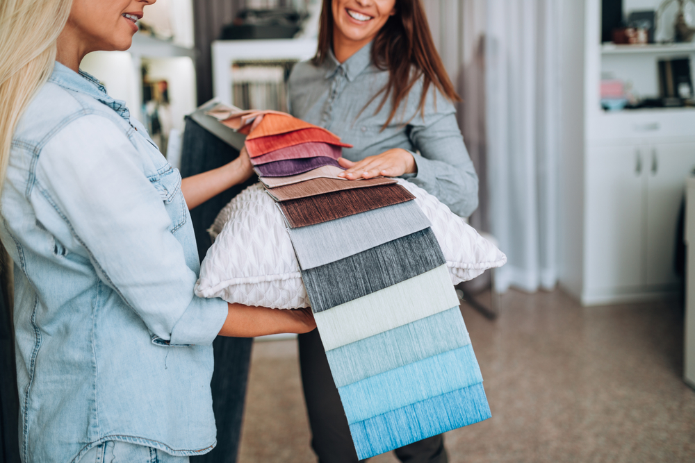 Woman talking to store worker about the different fabric options for blinds