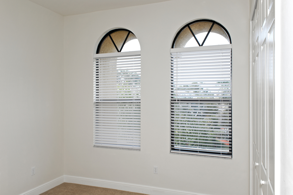 Two arched windows fitted with white venetian blinds