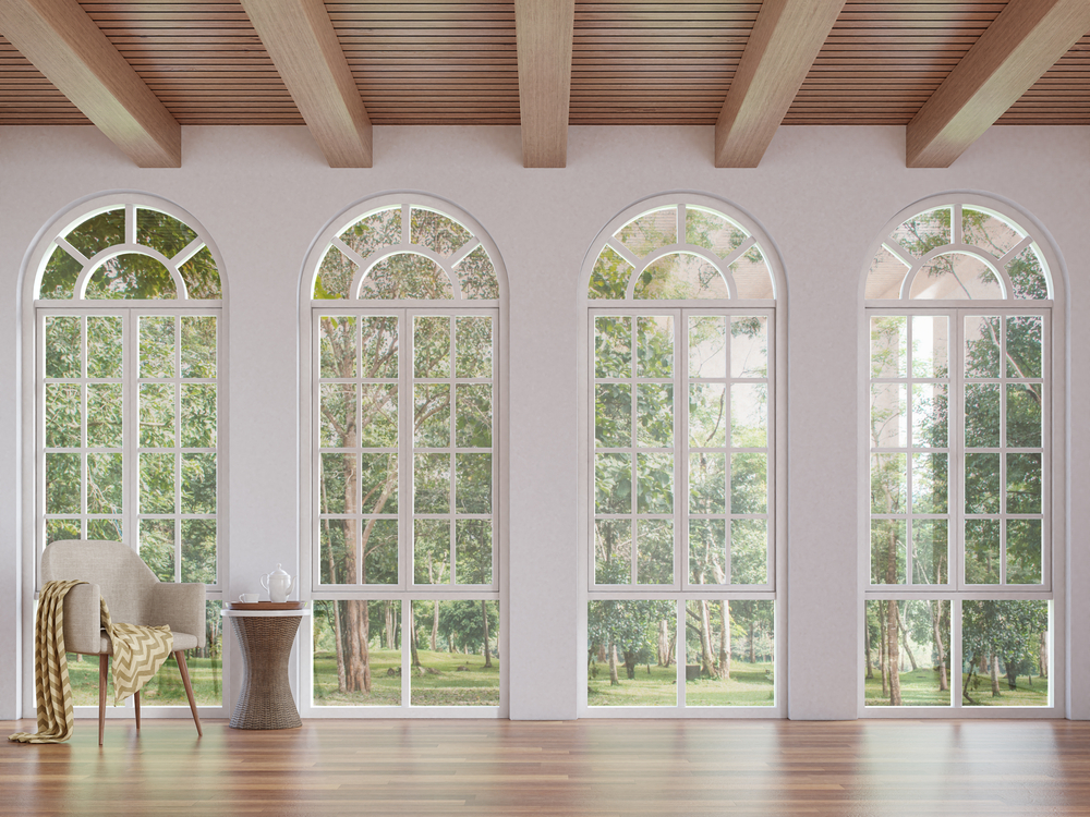Set of four arched windows with white frames in a white room with oak flooring