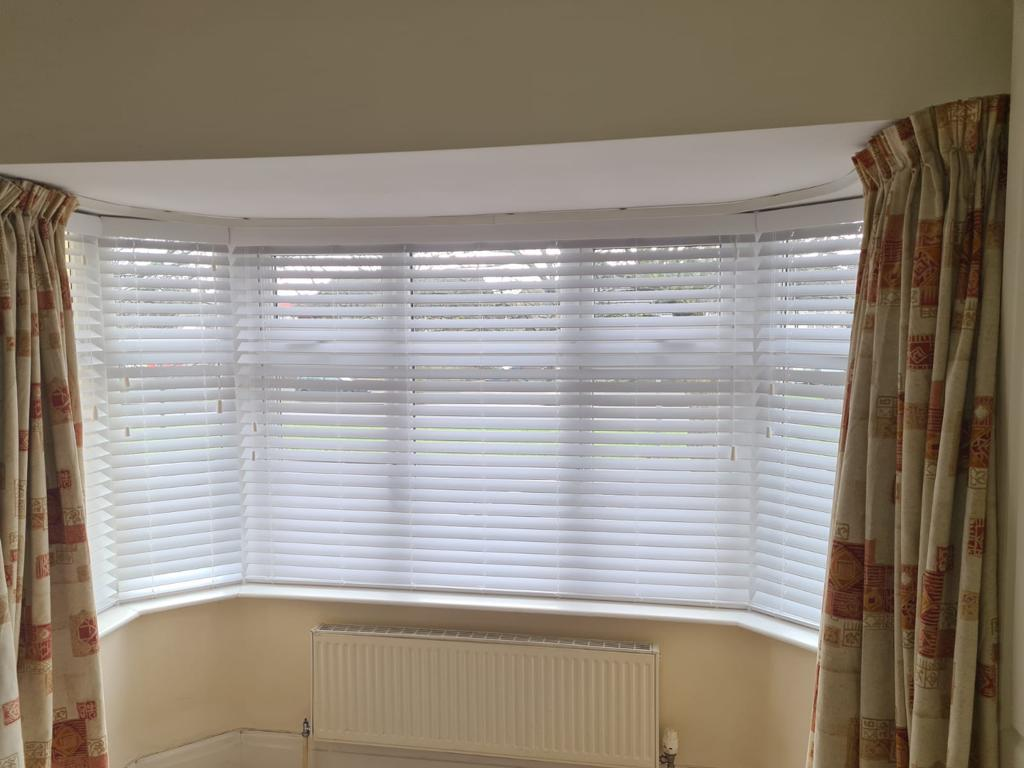White wooden Venetian blinds closed over a bay window with a radiator below and cream and red patterned curtains at each side.