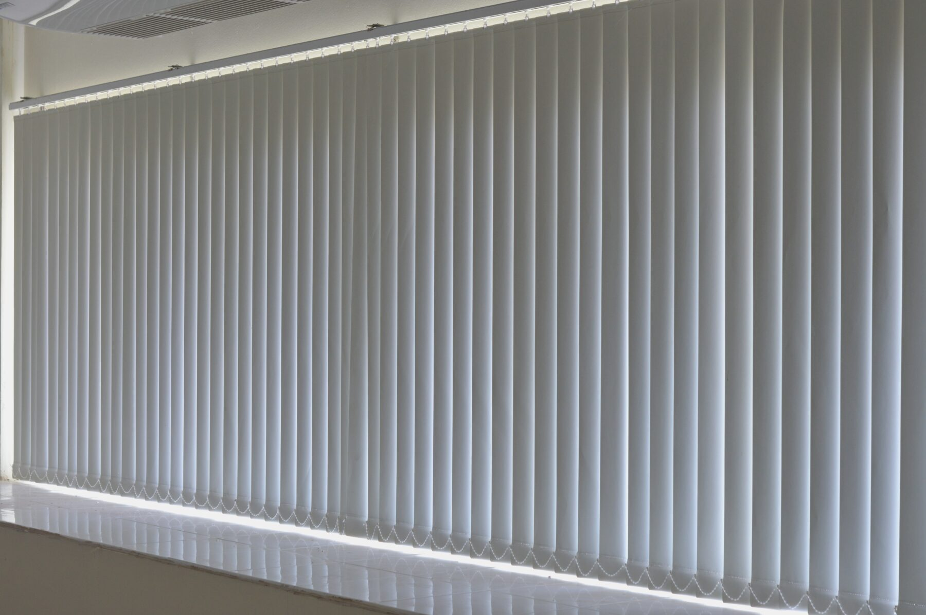 White vertical blinds closed over a wide window, with some light visible at the edges.