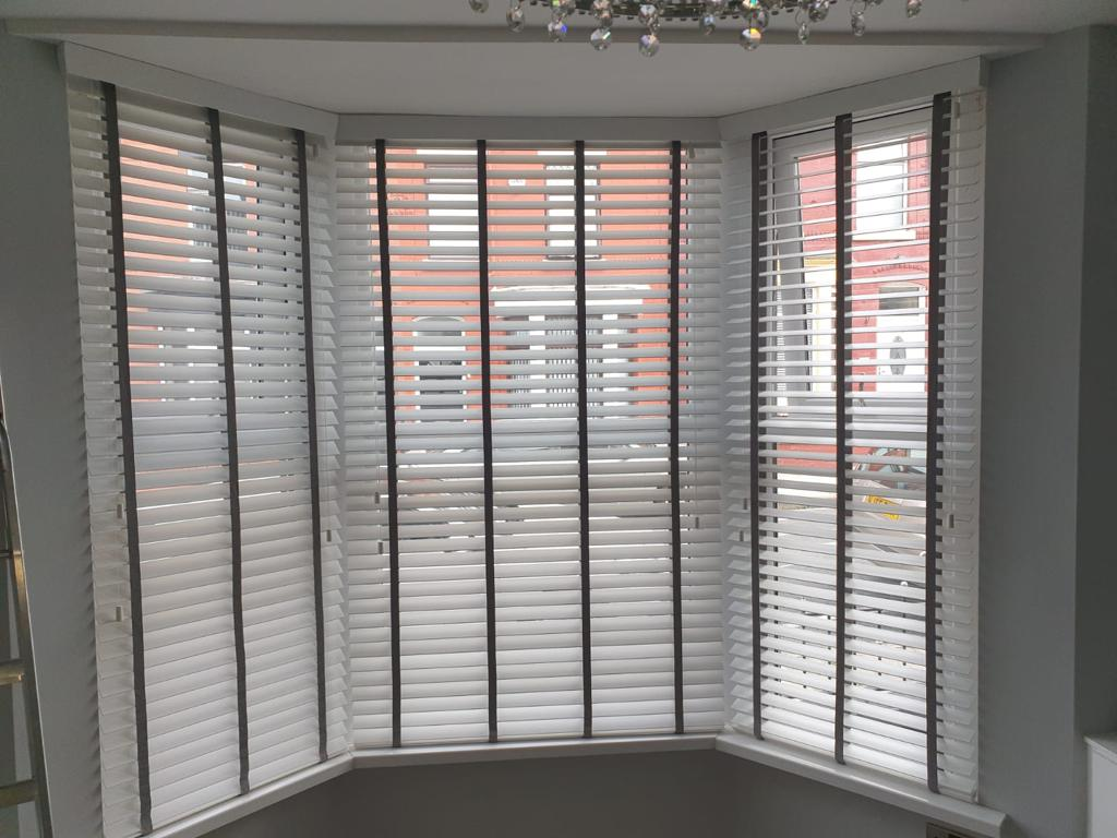 A bay window covered by white wooden Venetian blinds with black tapes, with the street outside and house opposite just visible through the slats.
