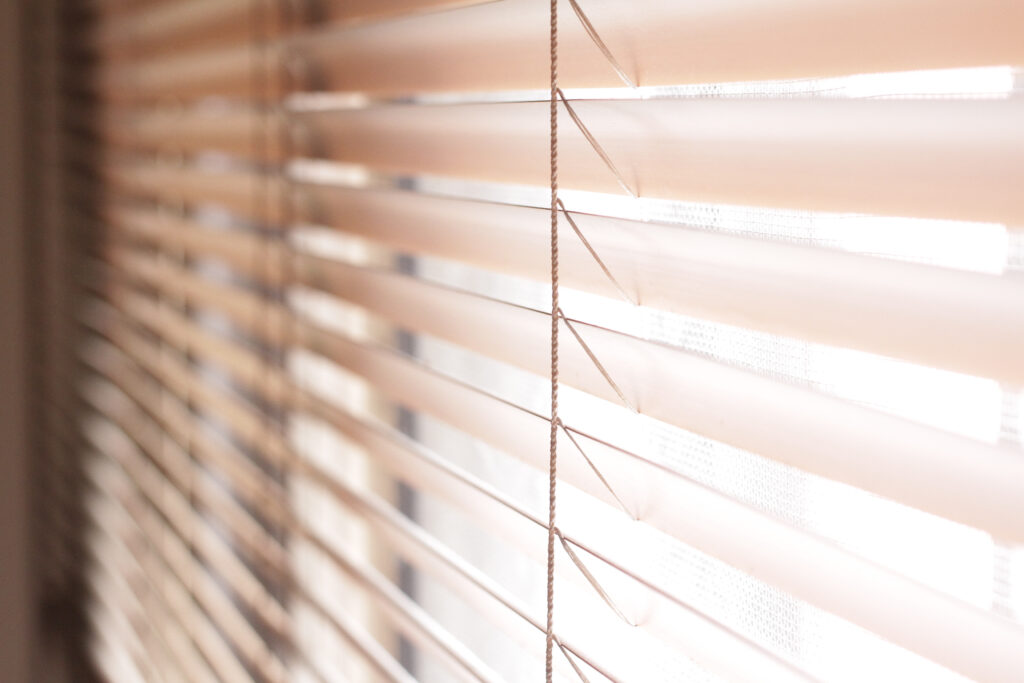 A closeup image of a set of brown vinyl blinds that are closed to stop the light from getting in.