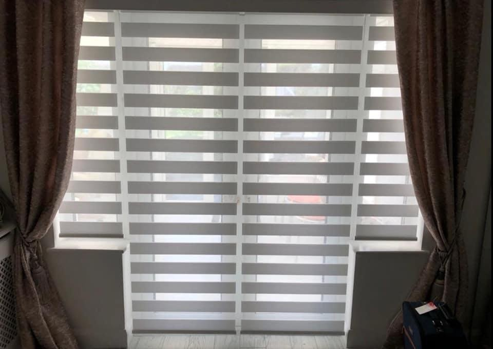 A set of day and night blinds that are fully closed to block out any light from entering the room.