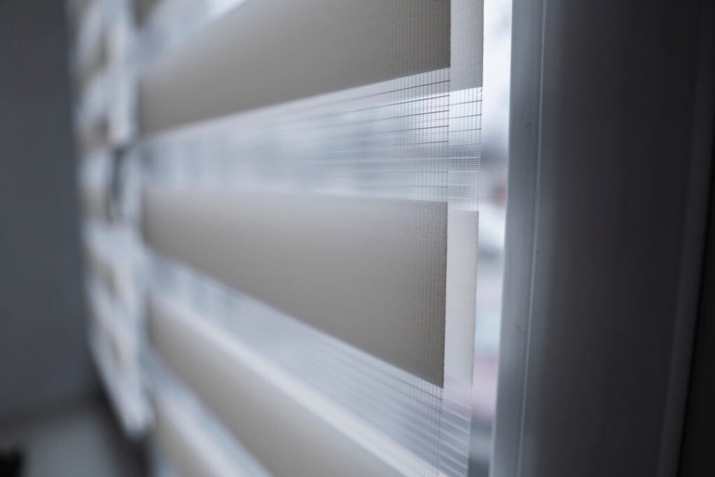 A close up image of a set of fabric roller blinds that are fully closed to stop the light from entering the room.