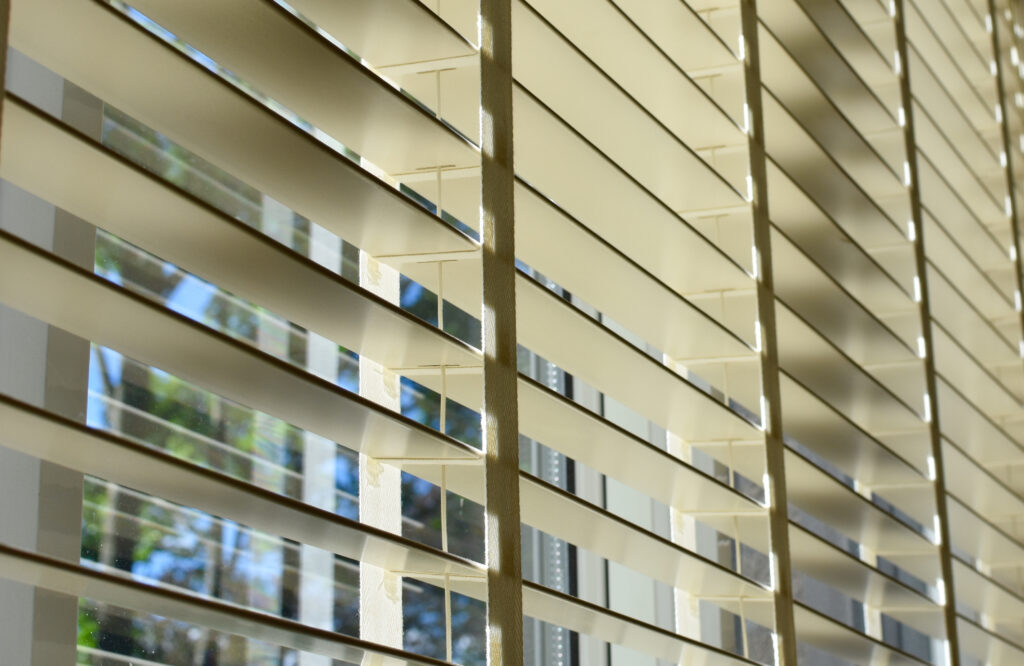 A closeup image of a set of horizontal faux wood blinds. Half open to allow some light to shine through.