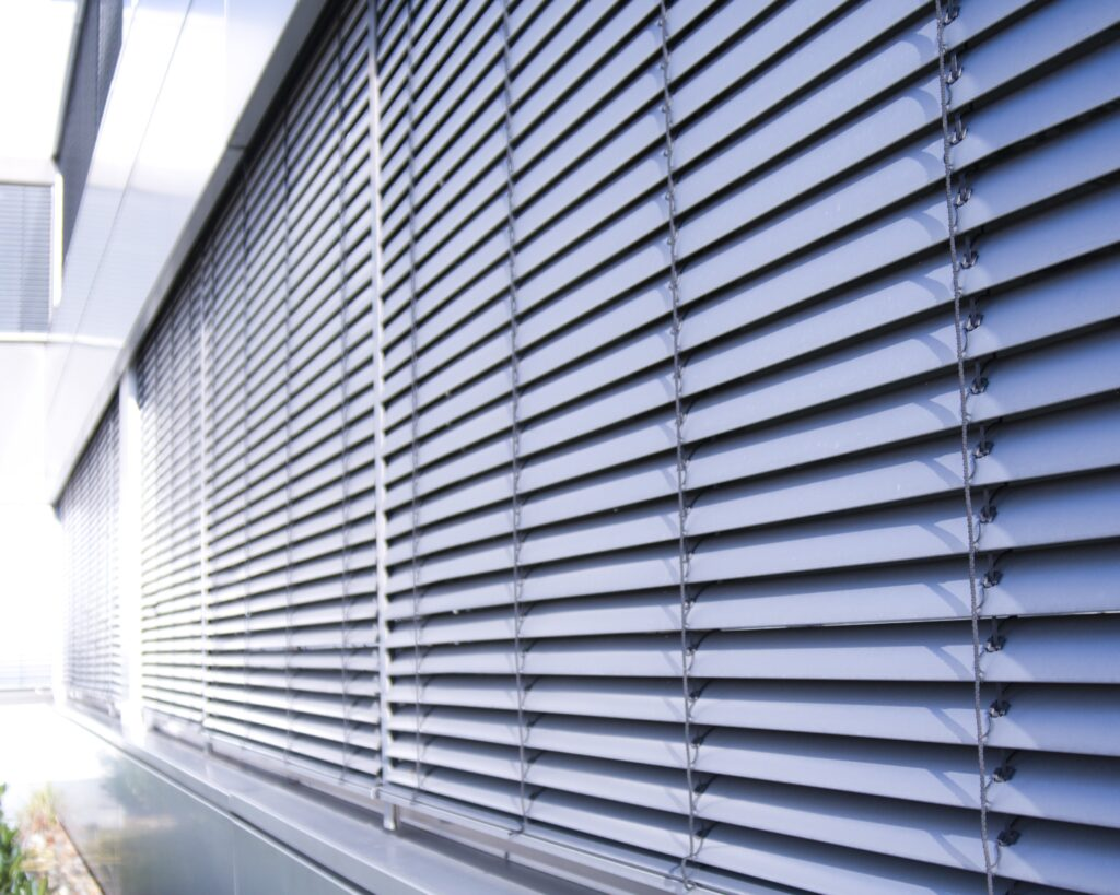 A set of closed aluminium metal blinds that are closed from the outside.