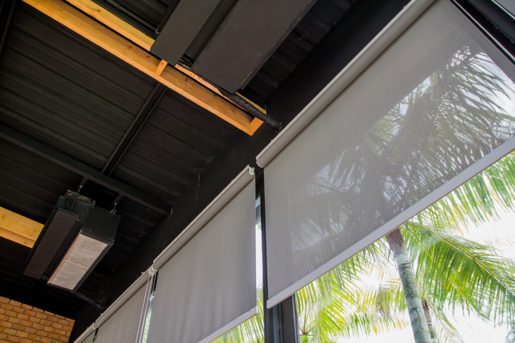 A set of natural material roller blinds that are half open to allow the sun from slightly entering the room.