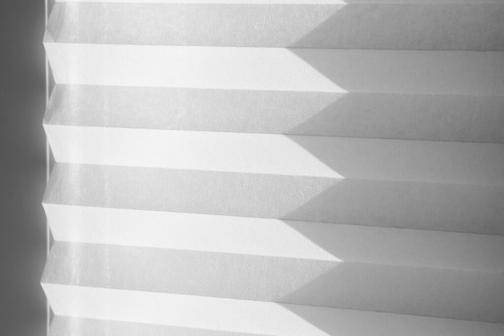 A set of paper blinds with a shadow being cast over them.