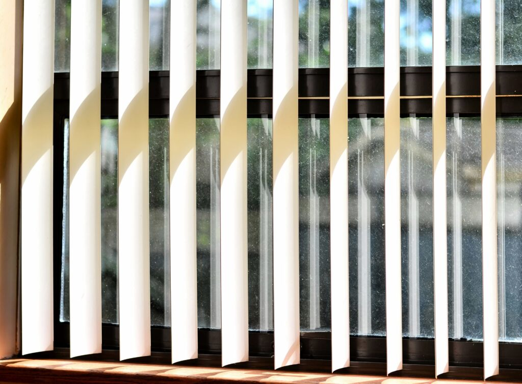 A close up set of plastic blinds that are open to allow light from getting inside the room.