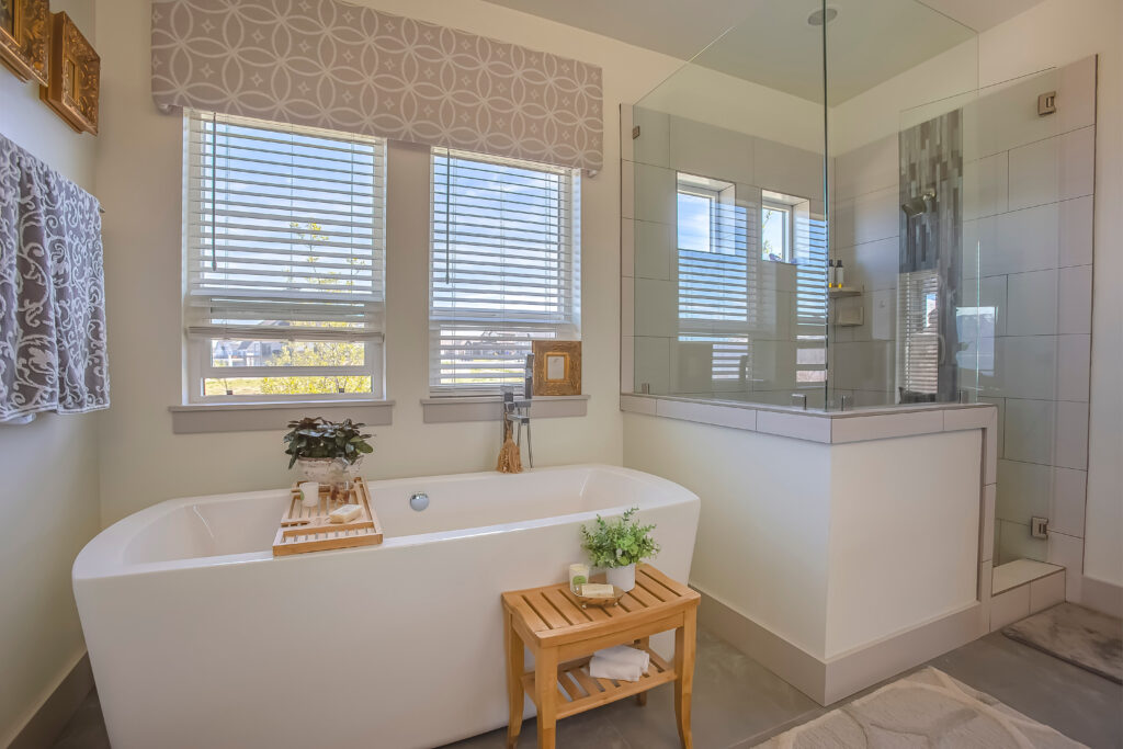 A modern bathroom with a set of real wood blinds sitting behind the bathtub.