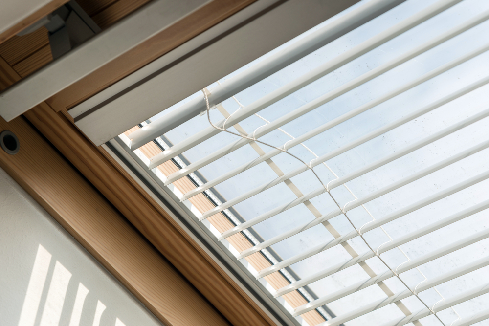 A pair of skylight blinds that are open to allow light in the room.