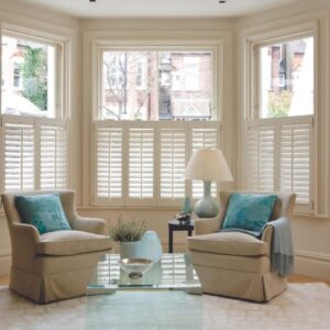 A pair of cafe-style shutters displayed on the lower part of large windows in a living room.