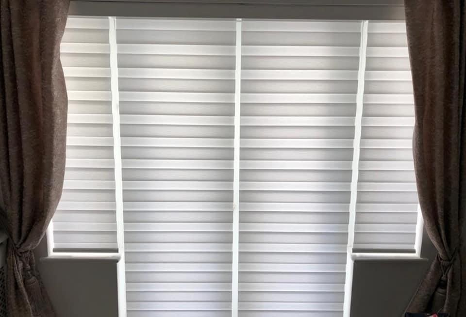 A set of closed day and night blinds inside a living room beside a pair of dark curtains.