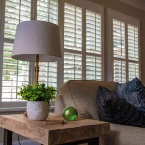 A pair of full-height shutters installed on a large window frame in a living room.
