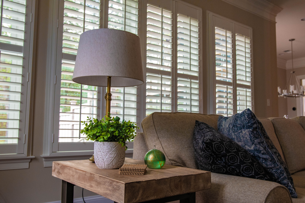 A pair of shutters placed on a high frame window with the blinds being open to allow light in the living room.