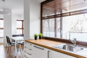 A set of kitchen blinds displayed on a set of windows overlooking a garden area.