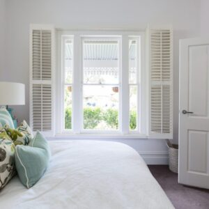 A pair of tier on tier shutterrs displayed in a bedroom.