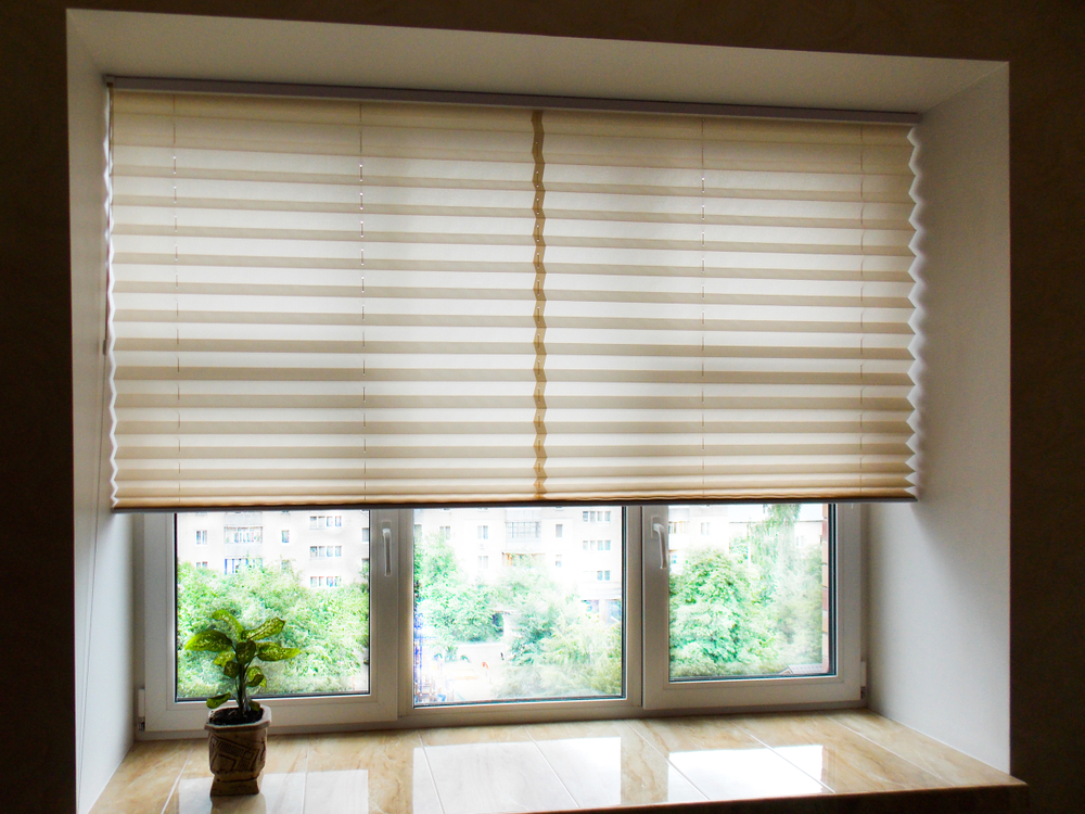A pair of cellular blinds halfway closed to allow a small amount of light through the room.