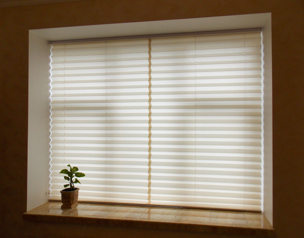 A pair of closed cellular blinds blocking out the light from entering the room.