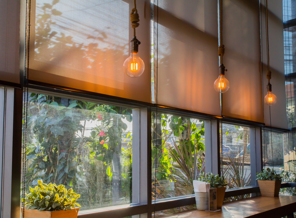 A set of fabric roller blinds half rolled down with decorative lights displayed next to them to provide a soothing beige/brown atmosphere.