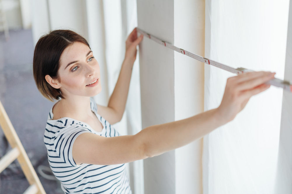 A woman measuring her windows in order to purchase fabric blinds.