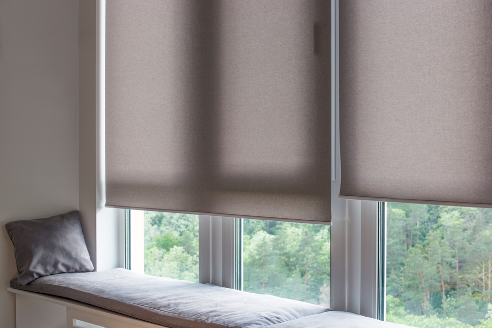A pair of motorised fabric roller blinds