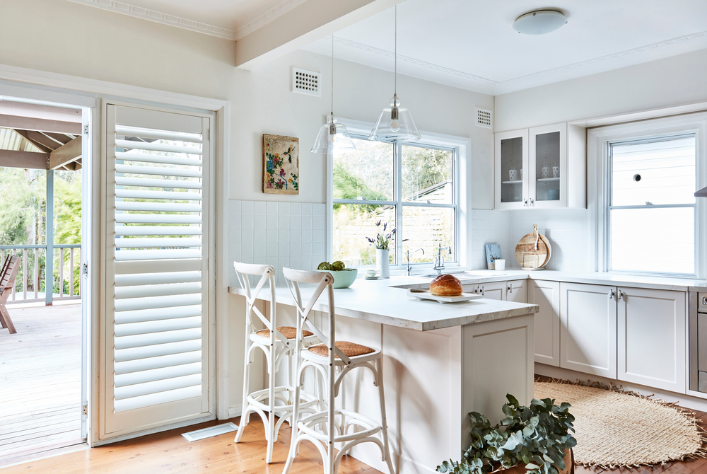 A pair of plantation shutters in a kitchen overlooking the garden area.