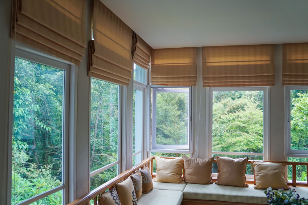 A pair of brown roman blinds displayed on a set of windows, overlooking stunning trees in an open space.